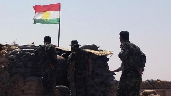 Members of Kurdish Peshmerga force stand guard at Sulaiman Pek front line