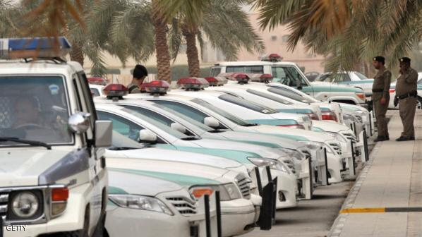 Saudi police cars are parked and policem